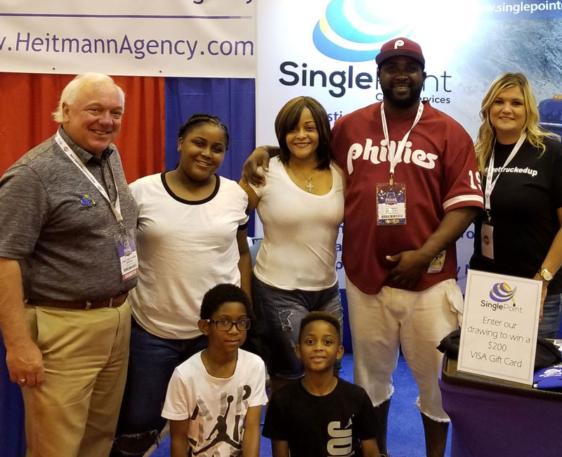 CEO of Single Point Carrier Services Next To Trucker and Family At The Texas Trucking Show
